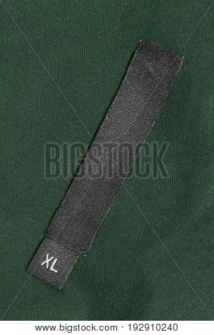 XL size clothes label on dark green cotton as a background
