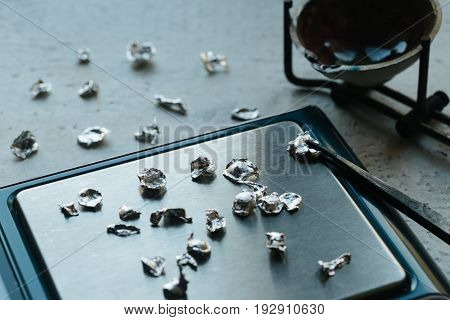 Jewelry tools. Jewellery. Goldsmith workplace workspace on light background. Hand craft. Workshop. Manufacturing. Weigh-scales with granules of metal silver and platinum. Closeup. Toned