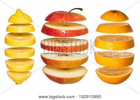Creative concept with Flying fruits. Sliced orange, lemon, apple isolated on white