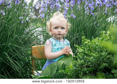 Little girl is sitting on a chair in the garden.