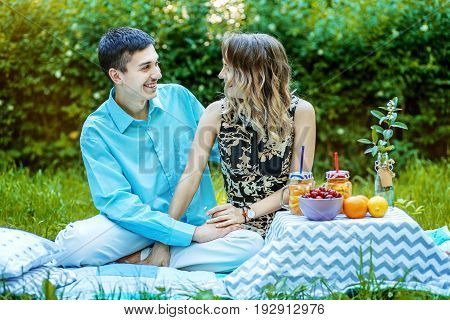 Young lovers have a couple on the picnic. Guy and girl in the park. The concept is love family lifestyle.