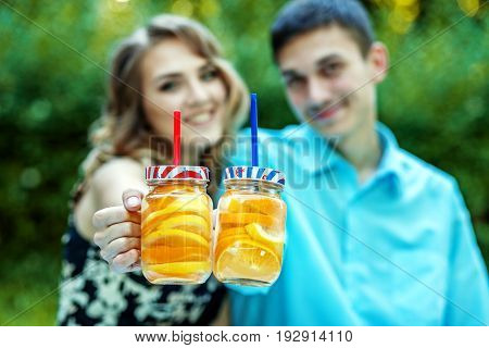 Detox water with orange and lemon. The guy and the girl hold the lemonade. The concept is healthy food lifestyle and summer.