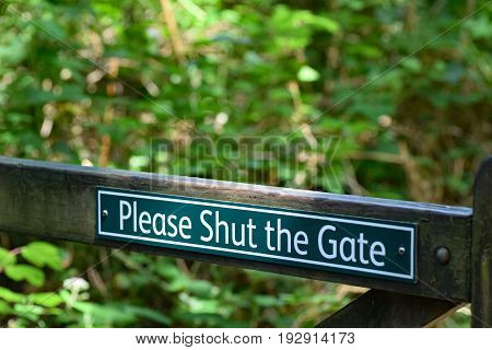 A polite Please shut the gate sign on a forest public footpath in North Devon England.