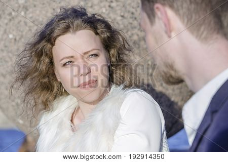 woman squints up from the evening sun looking at her man