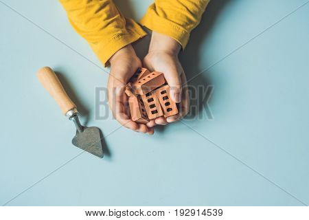 Close Up Of Child's Hands Playing With Real Small Clay Bricks At The Table. Toddler Having Fun And B