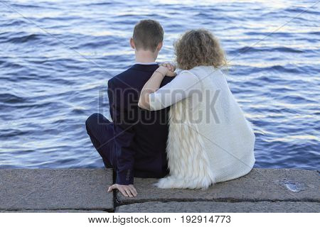 Young couple sitting on the waterfront right by the water