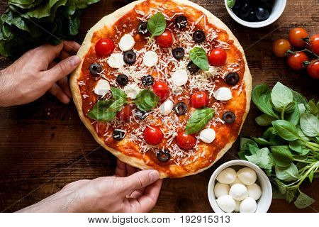 Pizza with tomatoes, mozzarella cheese, black olives and basil. Delicious italian pizza on wooden pizza board. Hands holding homemade pizza. Table top view