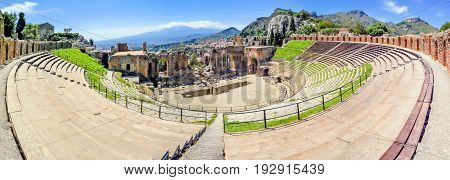 panoramic view of the ancient theater in Taormina with volcano Etna in the distance