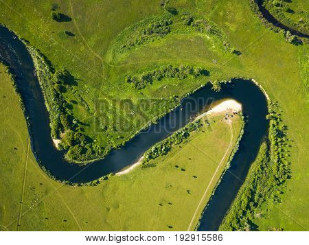 Top view of the Seim River (Ukraine) surrounded by trees and meadows on its banks view from the top - aerial photo