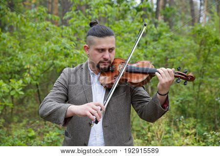 Handsome young man playing the violin on nature background