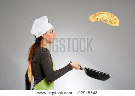 Young woman cook flipping pancake in the pan