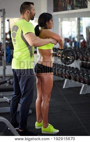 Personal trainer at work assisting a young woman in the gym