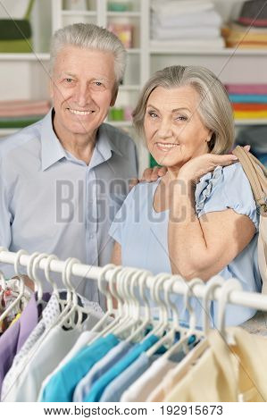 Portrait of a senior couple choosing shirt in shop