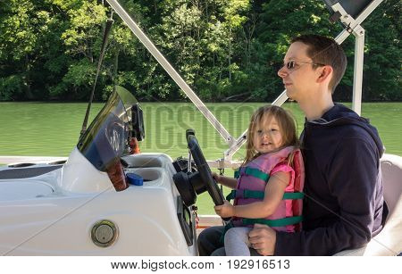 Father and young daughter driving a speedboat on a lake in summer while wearing a life jacket