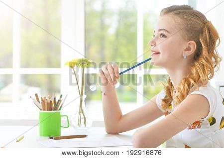 Pretty little girl sitting at kitchen table and drawing with pencils