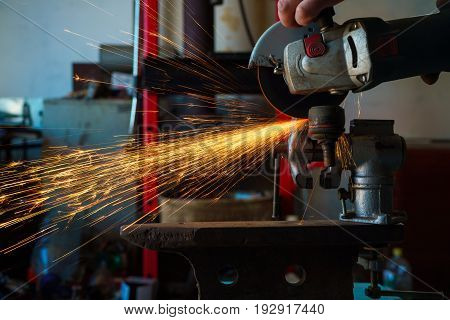 Angular grinding machine is cutting the metal and a lot of sparks flying around