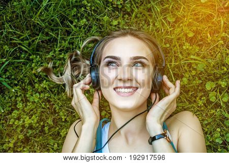 A cheerful girl listens to music with headphones. Park. Concept music lifestyle and learning.