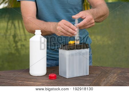 Filling a motorcycle battery with an acid
