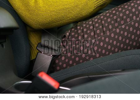 Close up of woman fastening car safety seat belt while sitting inside of vehicle before driving