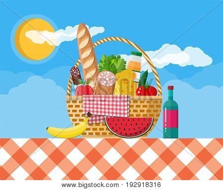 WIcker picnic basket with gingham blanket full of products. Bottle of wine, sausage, bacon, cheese, apple, tomato, cucumber, salad, orange juice. Vector illustration in flat style