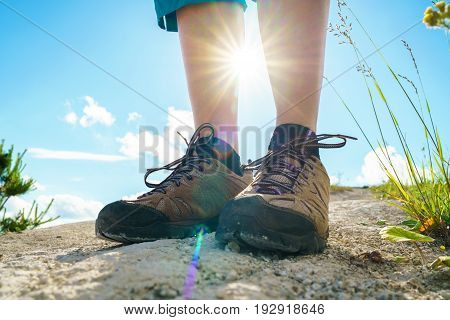 Legs of woman in tourist boots close-up. Hiking with a backpack over hilly terrain
