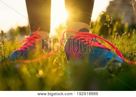 Running shoes - woman tying shoe laces. Closeup of female sport fitness runner getting ready for jogging outdoors