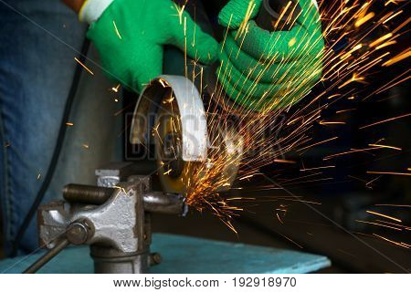 Worker with angular grinding machine is cutting the metal and a lot of sparks flying around poster