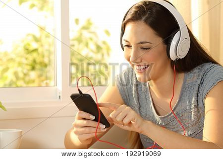 Portrait of a girl listening music on line selecting a song in a smart phone at home
