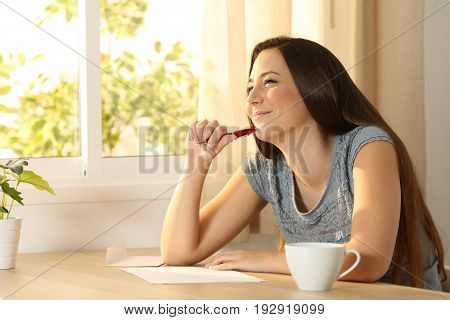 Happy girl thinking before handwriting a letter on a table at home