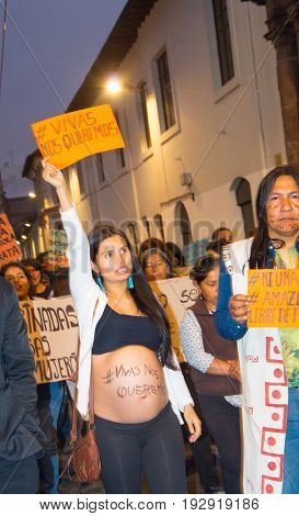 QUITO, ECUADOR- MAY 06, 2017: Unidentified pregnant woman with the slogan alive we want them writted in her belly, surrounded of people during the protest against the femicide in Quito Ecuador.