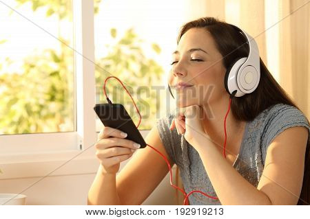 Relaxed woman listening music with headphones at home with a window in the background