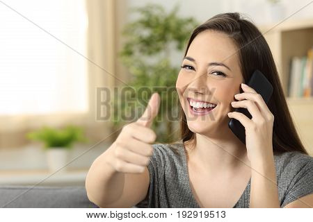 Woman talking on a phone call looking at you sitting on a sofa in the living room at home