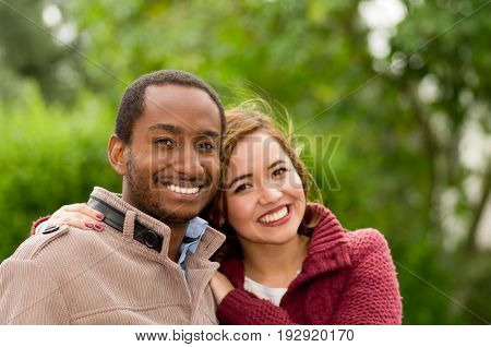 Beautiful and smiling happy interracial young couple in park in outdoors.
