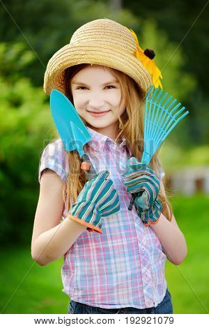 Adorable Little Girl Wearing Straw Hat And Childrens Garden Gloves Holding Garden Tools