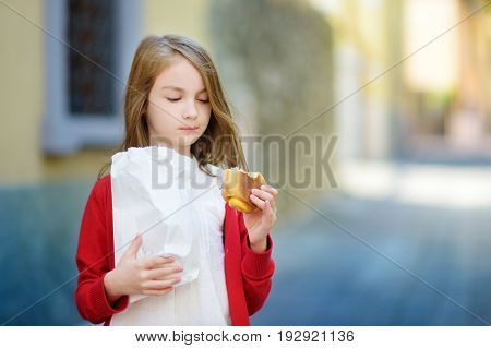 Adorable Little Girl Eating Fresh Baked Bun On Warm And Sunny Summer Day In Toscolano-maderno Town