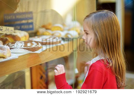 Adorable Little Girl Looking At Fresh Baked Buns On Warm And Sunny Summer Day In Toscolano-maderno T
