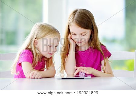 Two Adorable Little Sisters Playing With A Digital Tablet At Home. Child In An Elementary School.