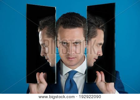 Man with three faces in two mirrors. Reflections of handsome businessman or manager with blue tie on red background. Agile business. Male beauty