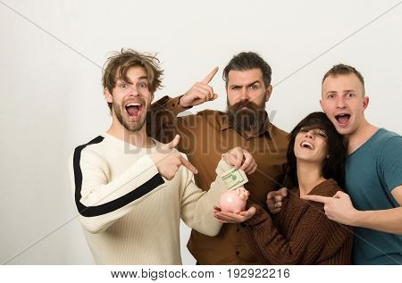 savings. Excited group of friends or people pretty girl or cute woman and three men in casual wear pointing at dollars money in piggy bank on white background budget finance cash and moneybox poster
