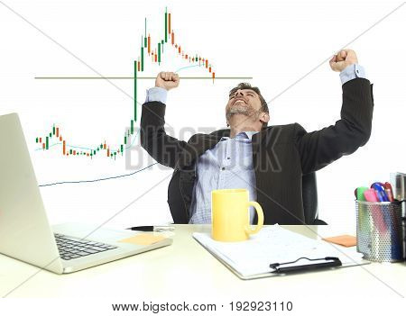 young attractive businessman crazy happy after winning forex or stocks trade sitting at office computer desk celebrating in business market trading success concept isolated on white background