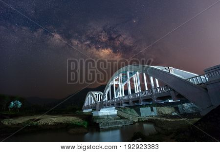 Beautiful Night Starry sky with Rising Milky Way over the bridge Thailand