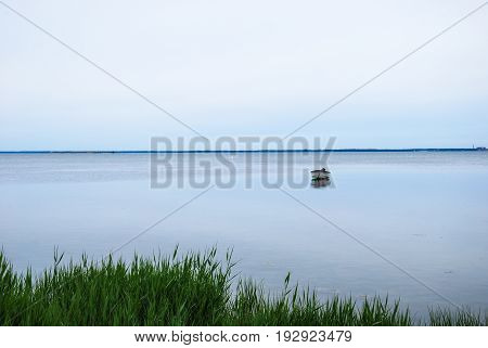 Solitude small boat in calm water by the coast of the swedish island Oland in the Baltic Sea