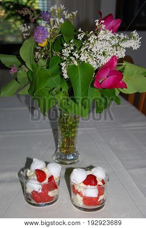 Two cups with strawberry desserts on a table decorated with a bouquet of summer flowers