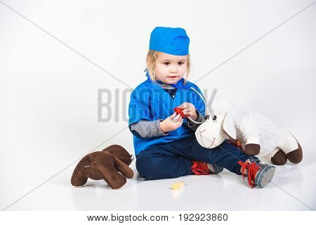 Vet Kid In Uniform Playing Doctor With Toy Animal