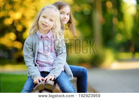 Two Adorable Little Sisters Laughing And Hugging On Summer Day In A Park