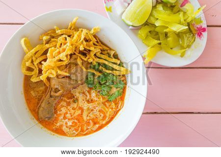 Noodle Khao soi - Traditional Thai Food Yellow noodles in a Thai red curry with chicken on wood Background. Khao soy is famous northern Thai food.