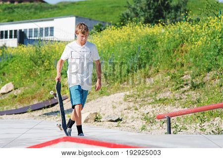 The boy is walking along the skate park with a skateboard in his hands