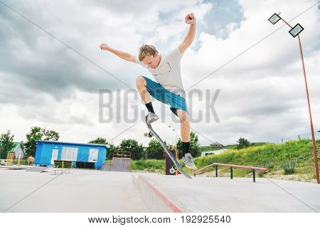Boy skateboarder in a skate park doing an ollie trick on a skateboard against a sky and thunderclouds