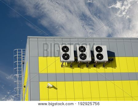 Air compressors installed on industrial building outdoors with sky background.