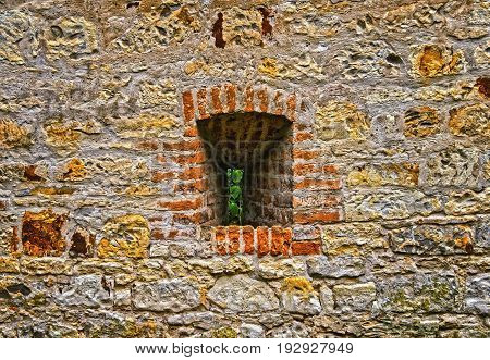 Window Or Loophole In Ancient Wall Built Of Irregular Stones.